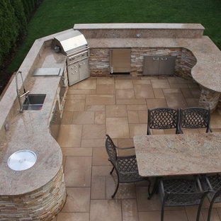 Inspiration for a mid-sized modern backyard stone patio kitchen remodel in New York with no cover