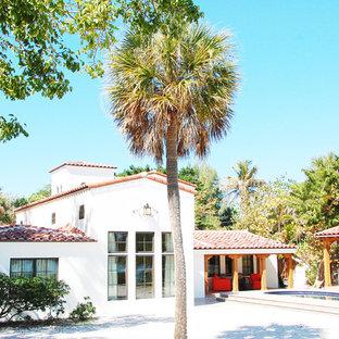 Foto di un patio o portico mediterraneo di medie dimensioni e dietro casa con un focolare, piastrelle e un tetto a sbalzo