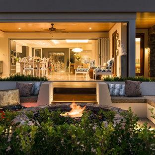 Esempio di un grande patio o portico country davanti casa con un focolare, nessuna copertura e graniglia di granito