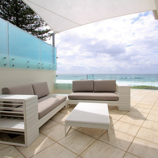 Inspiration for a large coastal courtyard patio in Brisbane with an awning, an outdoor kitchen and natural stone paving.
