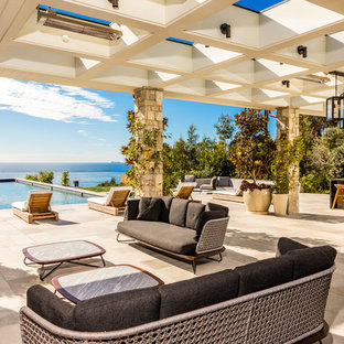 Inspiration for a beach style backyard stone patio remodel in Los Angeles with an awning