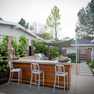 Large beach style back patio in Los Angeles with gravel, an outdoor kitchen and an awning.