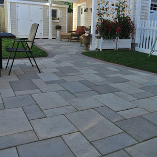 Design ideas for a small mediterranean back patio in Providence with concrete paving and an awning.