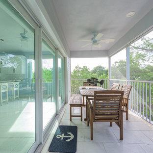 Esempio di un patio o portico stile marinaro di medie dimensioni e dietro casa con lastre di cemento e un tetto a sbalzo