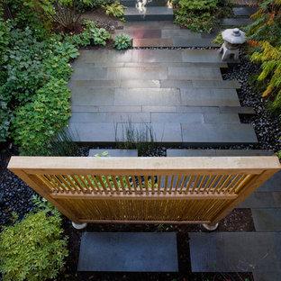 Immagine di un piccolo patio o portico etnico dietro casa con pavimentazioni in pietra naturale