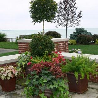 Modelo de patio tradicional, grande, en patio trasero, con adoquines de piedra natural y jardín de macetas