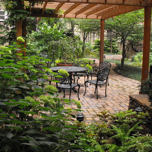 This is an example of a large traditional backyard patio in New York with a pergola and brick pavers.