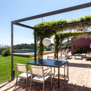 Modelo de patio contemporáneo con suelo de baldosas y pérgola