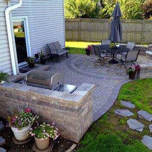 Aménagement d'une terrasse arrière classique de taille moyenne avec un foyer extérieur, des pavés en brique et aucune couverture.