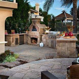 Design ideas for a medium sized mediterranean back patio in Other with an outdoor kitchen, natural stone paving and no cover.