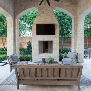 Example of a classic stone patio design in Houston with a roof extension and a fire pit