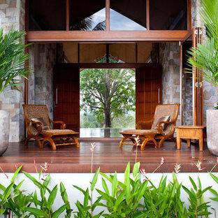 Foto di un ampio patio o portico tropicale dietro casa con fontane, pedane e un tetto a sbalzo