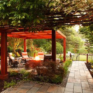 Exemple d'une terrasse arrière romantique avec un foyer extérieur, des pavés en pierre naturelle et une pergola.