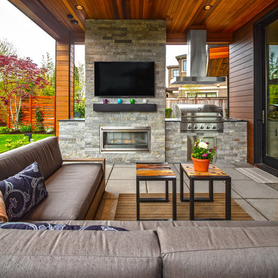 Trendy backyard concrete paver patio photo in Seattle with a roof extension
