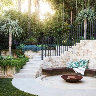 Ejemplo de patio exótico, sin cubierta, en patio trasero, con brasero y adoquines de piedra natural