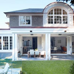 Foto di un grande patio o portico bohémian dietro casa con piastrelle e un tetto a sbalzo