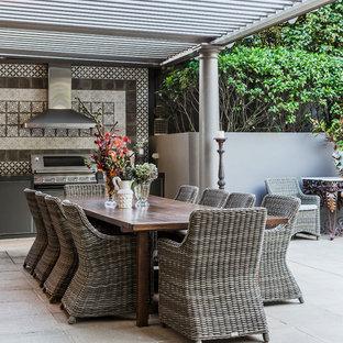 Imagen de patio bohemio, grande, en patio trasero, con cocina exterior, adoquines de piedra natural y pérgola