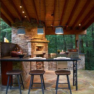 Modelo de patio rural, de tamaño medio, en patio trasero, con cocina exterior, adoquines de piedra natural y cenador