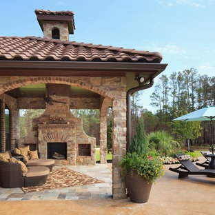 Inspiration for a mid-sized mediterranean backyard tile patio remodel in Houston with a fire pit and a roof extension