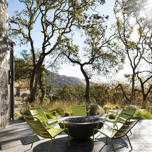 Foto di un patio o portico country in cortile con un focolare, piastrelle e nessuna copertura