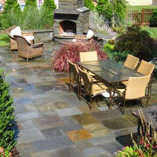 Modelo de patio tradicional, grande, sin cubierta, en patio trasero, con suelo de baldosas y brasero