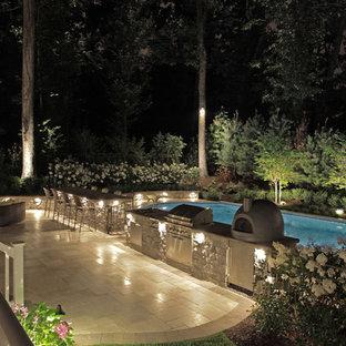 Immagine di un ampio patio o portico classico dietro casa con nessuna copertura e piastrelle