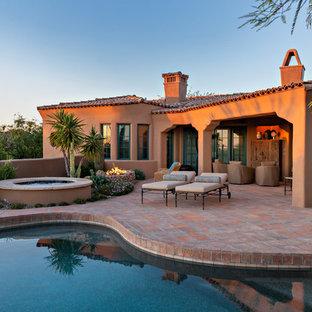 Réalisation d'une terrasse arrière sud-ouest américain avec un foyer extérieur et une extension de toiture.