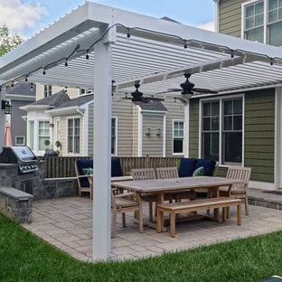 Ispirazione per un patio o portico stile americano di medie dimensioni con pavimentazioni in mattoni e una pergola