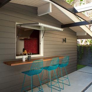 Immagine di un grande patio o portico minimalista dietro casa con lastre di cemento e un tetto a sbalzo
