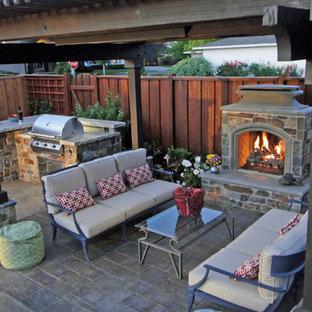 Foto di un patio o portico rustico di medie dimensioni e dietro casa con un focolare, cemento stampato e una pergola
