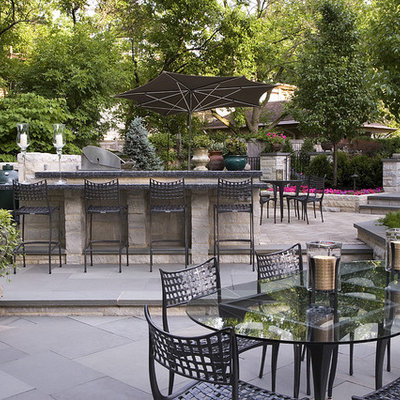 Patio kitchen - large traditional backyard stone patio kitchen idea in Chicago with no cover
