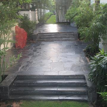 Black slate patio and red boulder side yard