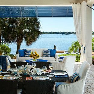 Cette photo montre une terrasse arrière bord de mer de taille moyenne avec une extension de toiture et des pavés en béton.