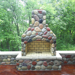 Blue River thin veneer outdoor fireplace - An outdoor fireplace with Blue River Natural Stone Veneer.  Installation by Casey Lonesk, stone supplied by Sturgis Materials.