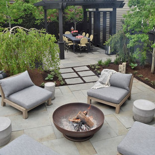 Inspiration for a small contemporary backyard stone patio remodel in Chicago with a fire pit and a pergola
