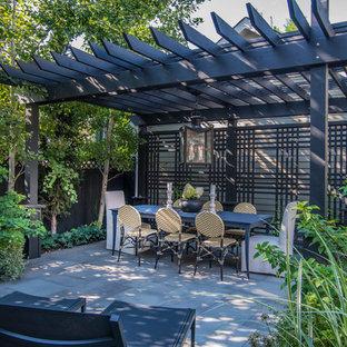 Esempio di un piccolo patio o portico minimal dietro casa con pavimentazioni in pietra naturale e una pergola