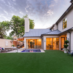 Large contemporary back patio in Dallas with a fire feature, decking and an awning.