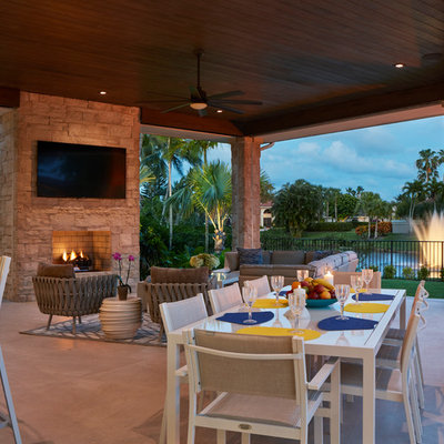 Inspiration for a contemporary backyard patio remodel in Miami with a roof extension and a fireplace