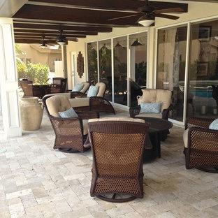 Ispirazione per un grande patio o portico boho chic dietro casa con un focolare, pavimentazioni in pietra naturale e un tetto a sbalzo
