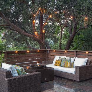 Ispirazione per un patio o portico eclettico con un focolare, piastrelle e nessuna copertura