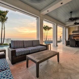 Immagine di un grande patio o portico costiero dietro casa con un tetto a sbalzo e pavimentazioni in cemento