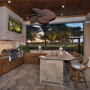 Photo of a large mediterranean back patio in Miami with an outdoor kitchen, natural stone paving and a roof extension.