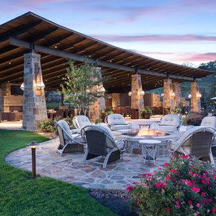 Foto di un ampio patio o portico stile americano dietro casa con pavimentazioni in cemento e un tetto a sbalzo