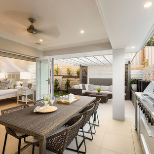 Design ideas for a beach style backyard patio in Brisbane with an outdoor kitchen and a roof extension.