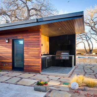 Ispirazione per un ampio patio o portico design dietro casa con pavimentazioni in pietra naturale e un tetto a sbalzo