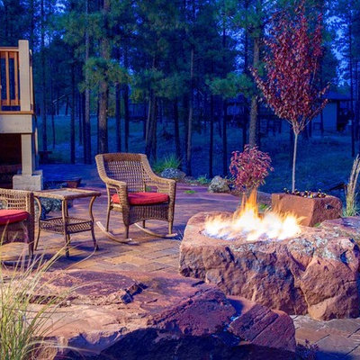 Example of a mid-sized mountain style backyard brick patio design in Denver with a fire pit and no cover
