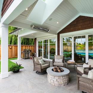 Immagine di un patio o portico stile marino di medie dimensioni e dietro casa con un focolare, piastrelle e un tetto a sbalzo