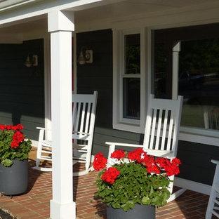 Foto di un patio o portico country di medie dimensioni e davanti casa con un giardino in vaso, pavimentazioni in mattoni e un tetto a sbalzo