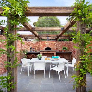 Ejemplo de patio tradicional, en patio trasero, con cocina exterior y pérgola
