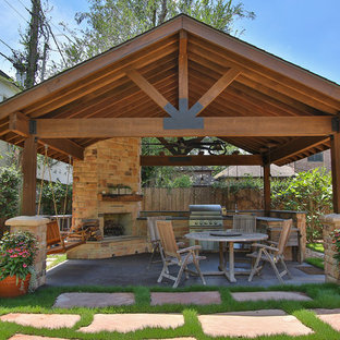 Large mountain style backyard concrete patio kitchen photo in Houston with a gazebo